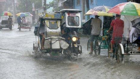 Residents commute along a flooded stretch of road during heavy rain in the suburbs of Manila on 12 August 2013