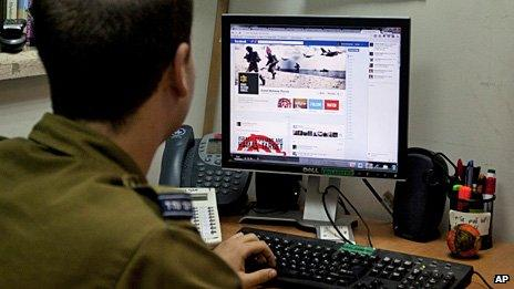 A member of the Israeli Defense Force looks at its Facebook site