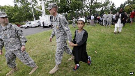 A young Afghan villager boy named Khan holds the hand of US Army Master Sgt Timothy Gunther after a news conference at Joint Base Lewis-McChord, Washington state, on 23 August 2013