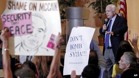 Members of the crowd hold up signs against military action in Syria as US Senator John McCain speaks in Phoenix, Arizona, on 5 September 2013