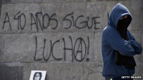 """A man stands in front of a graffiti reading """"40 years after, the fight continues"""" during a demonstration opposing the coup in Santiago on 8 September, 2013"""