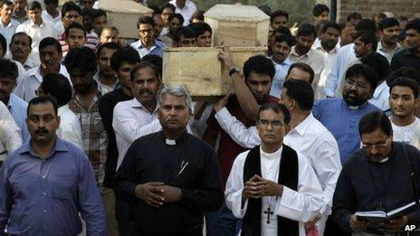 Pakistanis carry coffins during the funeral of victims of a suicide attack on a church in Peshawar, Pakistan, Tuesday, Sept. 24, 2013.