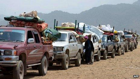 An Internally Displaced Person stands alongside a convoy of vehicles prior to the start of the journey to their home town after an army operation against militants was completed at the Kurram Agency, in Parachamkani on June 29, 2013.