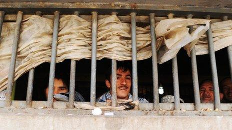 Afghan prisoners look on through bars during a visit by local and international media at Pul-e Charkhi prison on the outskirts of Kabul on March 7, 2010