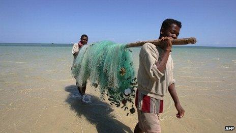 Fishermen carry fishing nets on a beach - Madagascar, 2006