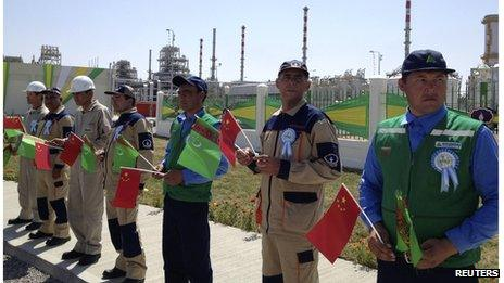Workers hold Chinese and Turkmenistan state flags as they attend a launching ceremony at Galkynysh gas field in eastern Turkmenistan (4 September 2013)