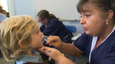Nurse giving nasal spray to a school pupil