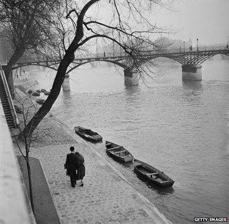 January 1954 - a couple walks on the bank of the Seine