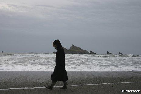 Woman walking along shore
