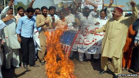 Protestors in Pakistan with a burning US flag