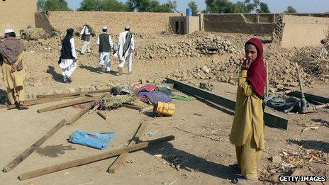 Villagers stand in rubble of a house