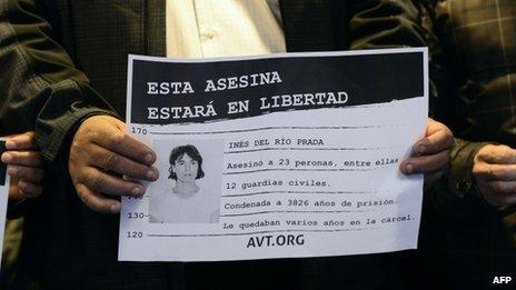 """An activist holds a placard which reads """"This murderer will be free"""", alongside a picture of Ines Del Rio"""