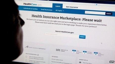 """A woman looks at the HealthCare.gov insurance exchange internet site showing a """"Please wait"""" page, in this 1 October 2013 file photo in Washington, DC"""