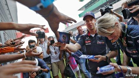 Red Bull F1 driver Sebastian Vettel of Germany hands out autographed pictures to his fans at the Buddh International Circuit on 24 Oct 2013