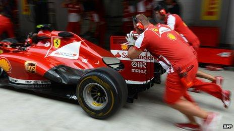 Members of the Ferrari team push a car into position in a pit lane during a drill at the Buddh International circuit, 24 Oct, 2013