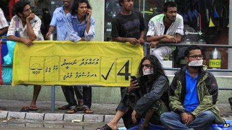 Supporter of Maldives former president Mohammed Nasheed with their mouths covered with tape sit near a campaign poster of Nasheed during a silent protest in Male, Maldives, Monday, Oct. 21, 2013