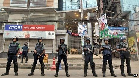 Bangladeshi police officials stand guard on a street during a general strike in Dhaka