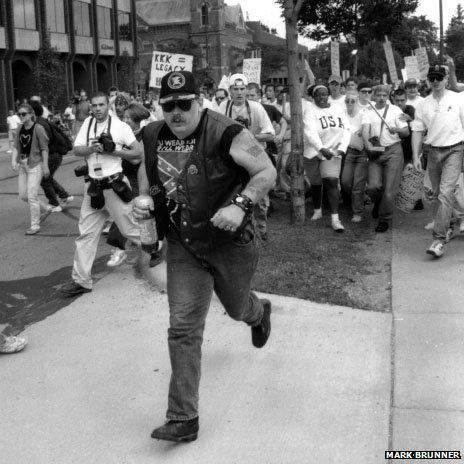 Man being chased by anti-KKK demonstrators