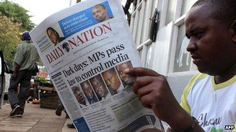 A man reading a paper about Kenya's new media bill, 1 November 2013