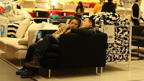 A couple sit on a sofa in Ikea