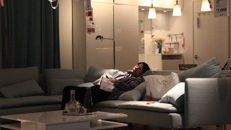 A man sleeps on a sofa in Ikea