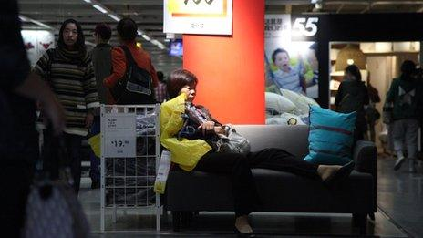 A woman sits on a sofa in Ikea