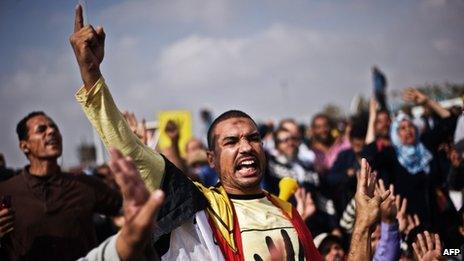 Supporters of ousted President Mohammed Morsi shout slogans in his support outside the Police Academy where his trial is taking place on November 4