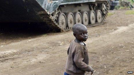 A young boy walks near a Democratic Republic of Congo army tank