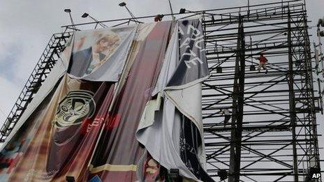 Filipino workers bring down a giant billboard along a busy highway as they prepare for Typhoon Haiyan in suburban Makati, south of Manila, Philippines, 7 Nov 2013