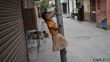 Indian street child climbing lamppost