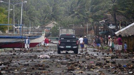Debris litters the road by a coastal village in Legazpi in the Philippines