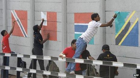 Sri Lankan volunteers paint national flags of Commonwealth nations on a wall in the capital Colombo