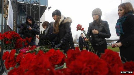 People lay flowers near the fence of Kazan airport