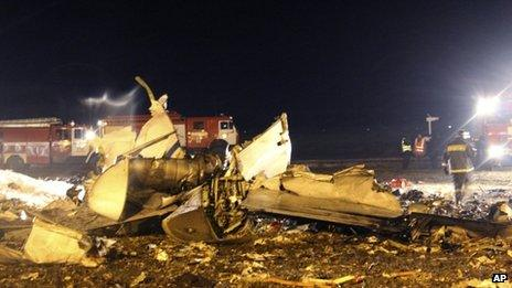 Fire fighters and rescuers work at the crash site