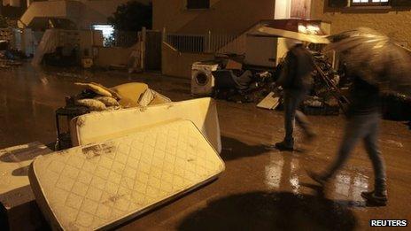 People walk in a flooded street in Olbia, north-eastern Sardinia