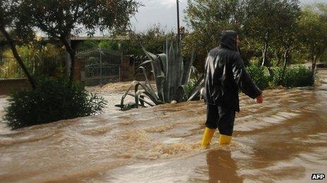 A man walks in a flooded street in Uras, central Sardinia