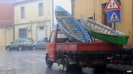 Boats are carried in a truck to give assistance to floods victims in Terralba, central Sardinia