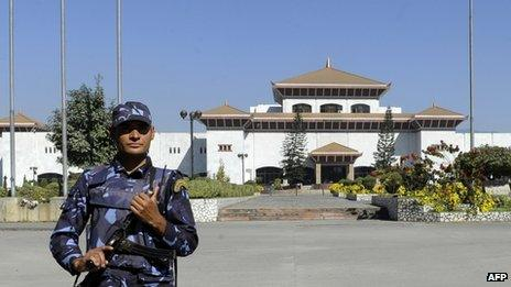 A police officer stands guard in front of the parliament building in Kathmandu (19 November 2013)