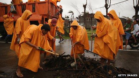 Workers clear part of the road near Bassey in Eastern Samar, Philippines (22 Nov. 2013)