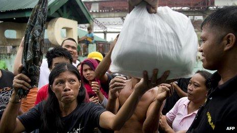 A woman receives a food parcel at a temporary shelter for super typhoon Haiyan victims in Tacloban on November 22, 2013