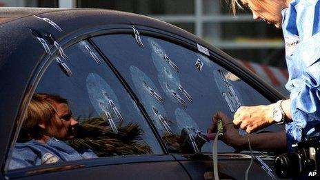 """Unidentified ballistics investigator comb the scene of Radovan Krejcir""""s bullet-proof car after he escaped an attempt to kill him in Johannesburg, South Africa, Wednesday July 24, 2013."""