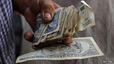 A farmer holds a wad of Cuban money