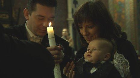 Andriy (left) watches his son being baptised in Lviv's cathedral