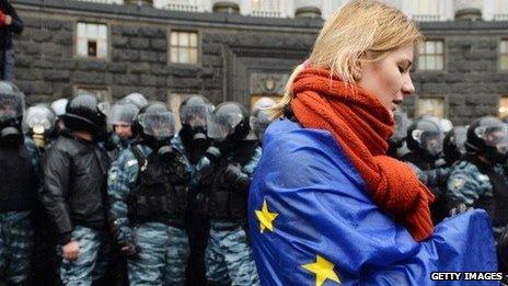 A Ukrainian woman draped in an EU flag stands in front of riot police during demonstrations in Kiev on November 25.