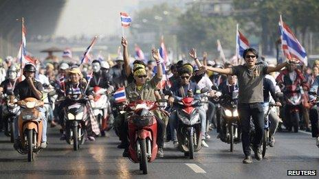 Anti-government protesters with Thai national flags ride their motorbikes as they rally on a main road in Bangkok, 9 December 2013