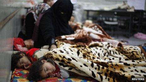 A child sleeps on a mattress at a school after being evacuated from his house in Khan Younis in the southern Gaza Strip (December 14, 2013)