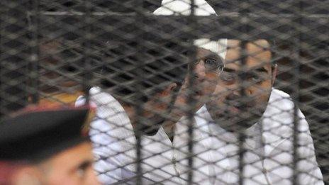 Political activists Ahmed Maher, Ahmed Douma (L) and Mohamed Adel (R) of the 6 April movement look on from behind bars in Abdeen court in Cairo, December 22, 2013.