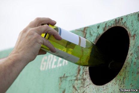 Dropping an empty wine bottle in the bottle bank
