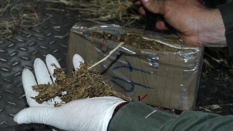 A policeman cuts open a package of marijuana in Villavicencio in April 2010