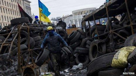 Anti-government protester carries tyres to reinforce barricades built to fend off riot police in Kiev, 28 January 2014